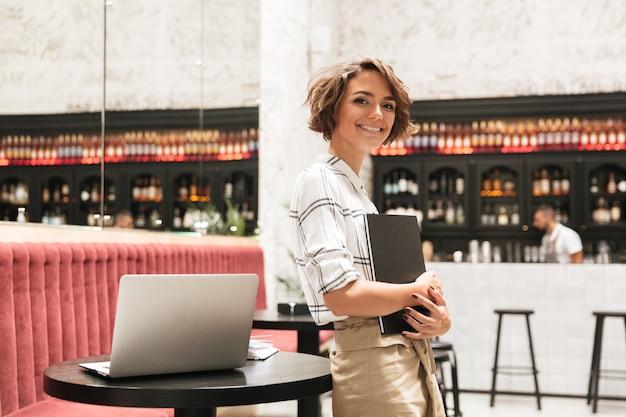 Vista lateral de sonriente mujer rizada de pie cerca de la mesa