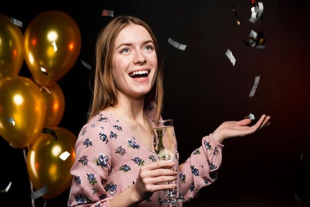 Vista lateral sonriente mujer sosteniendo una copa de champán