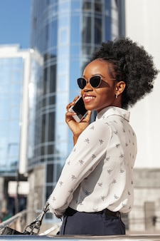 Vista lateral sonriente mujer con teléfono