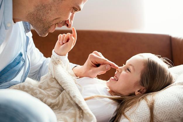Vista lateral de sonriente padre e hija divirtiéndose