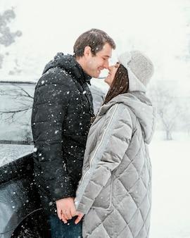 Vista lateral de la sonriente pareja besándose en la nieve durante un viaje por carretera
