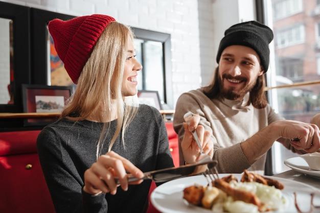 Vista lateral de la sonriente pareja comiendo en la cafetería