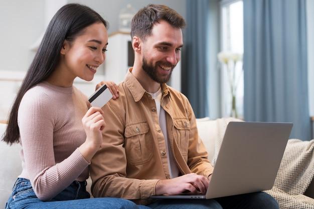 Vista lateral de la sonriente pareja de compras en línea