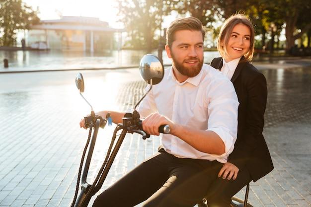 Vista lateral de la sonriente pareja de negocios monta en moto moderna