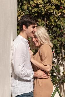Vista lateral de la sonriente pareja posando al aire libre
