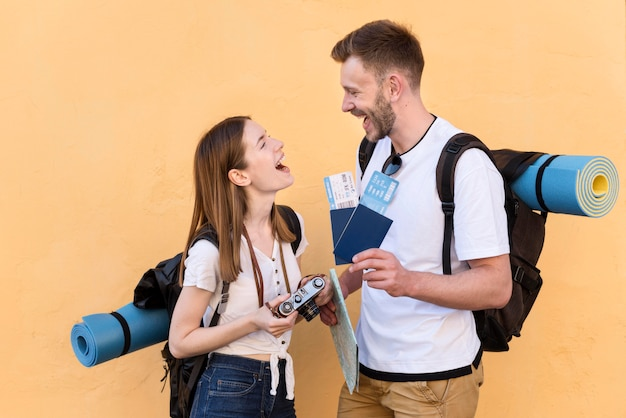 Vista lateral de la sonriente pareja de turistas con mochilas y pasaportes