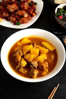 Vista lateral de sopa china con pollo y papas en placa
