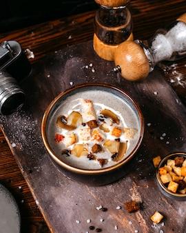 Vista lateral de la sopa de crema de champiñones con tostadas en un tazón