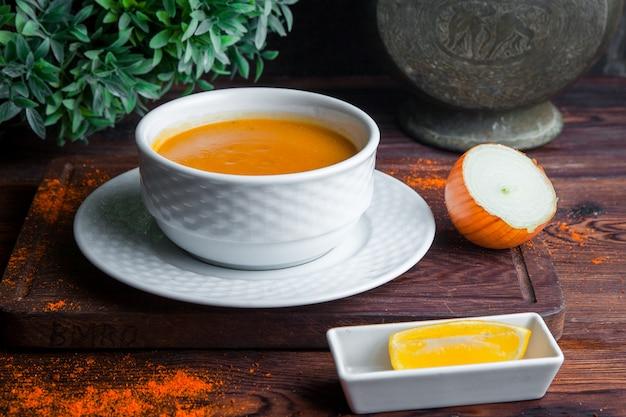 Vista lateral sopa de lentejas con cebolla y limón
