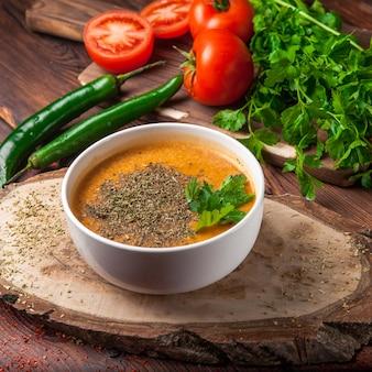 Vista lateral sopa de lentejas con pimiento verde y tomate y perejil en plato blanco