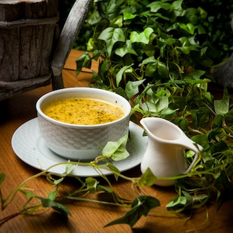 Vista lateral sopa de lentejas con vinagre y rama de uva en plato hondo