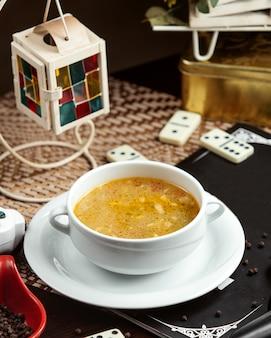 Vista lateral de sopa de pollo y dominó sobre la mesa
