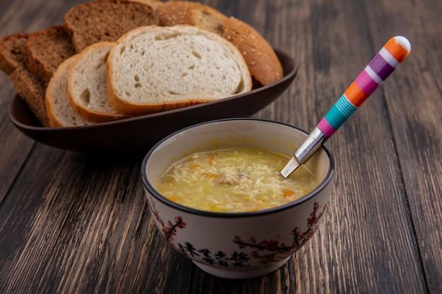 Vista lateral de la sopa de pollo orzo con una cuchara en un tazón y panes en rodajas de centeno blanco mazorca sembrada en un tazón sobre fondo de madera