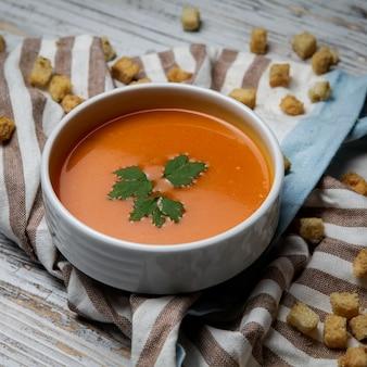 Vista lateral sopa de tomate con galletas y servilletas en plato blanco sobre mesa de madera