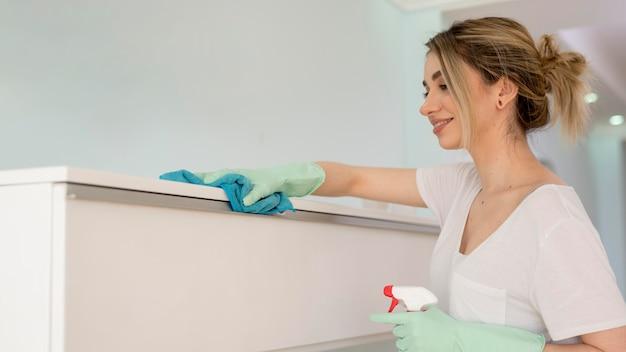 Vista lateral de la superficie de limpieza de la mujer con un paño