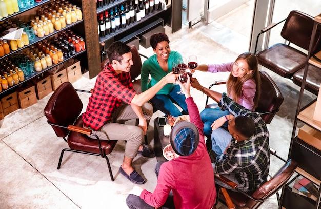Vista lateral superior de amigos ricos degustando vino tinto y divirtiéndose en la bodega del bar de moda