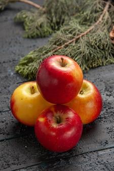 Vista lateral superior manzanas y ramas seis manzanas de color amarillo-rojo debajo de las ramas de abeto con conos en el centro de la mesa