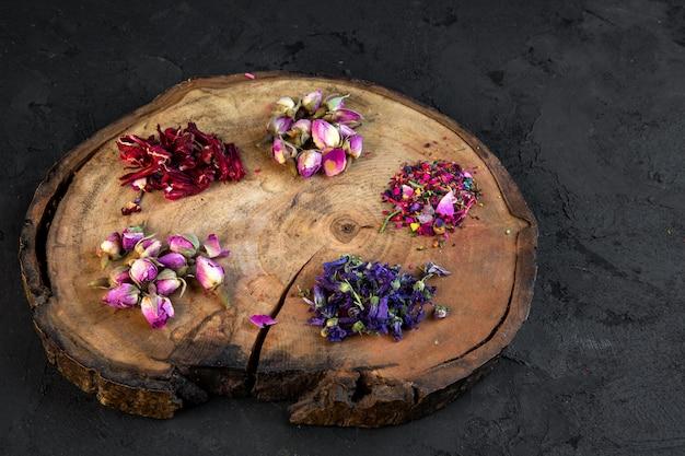 Vista lateral del surtido de hierbas secas y flores y té de rosas sobre tabla de madera sobre negro
