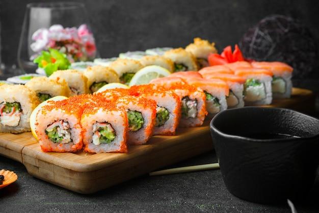 Vista lateral de sushi con salsa de soja y palillos en tabla de servir de madera