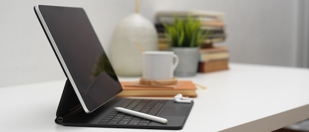 Vista lateral de la tableta digital con tableta en mesa blanca con suministros y decoraciones