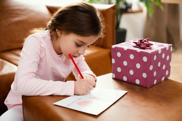 Vista lateral de la tarjeta de dibujo de la hija para el día del padre con presente
