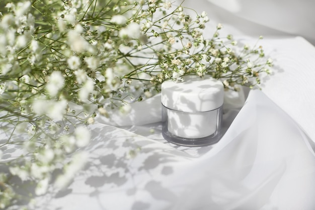 Vista lateral del tarro de crema blanca. cosmetología orgánica, concepto botánico de cosmética natural. producto para el cuidado de la piel de las mujeres. envase de plástico facial, bálsamo corporal y composición de follaje