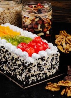 Vista lateral de la tarta de frutas con crema batida de cerezas kiwi y rodajas de naranja sobre la mesa