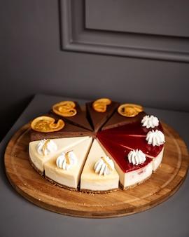 Vista lateral de la tarta de queso en rodajas sobre placa de madera, fruta de chocolate y rodajas de vainilla