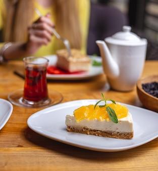 Vista lateral de tarta de queso servido con rodajas de naranja en un plato blanco