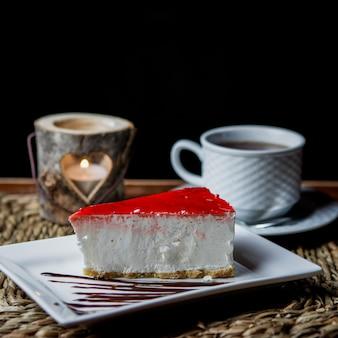 Vista lateral tarta de queso con una taza de té y velas en servilletas