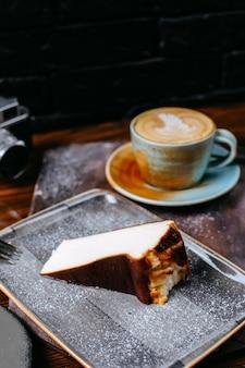 Vista lateral de una taza de café con leche servido con tarta de queso