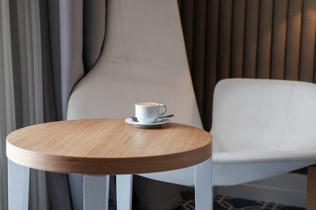 Vista lateral de la taza de café en una pequeña mesa redonda horizontal