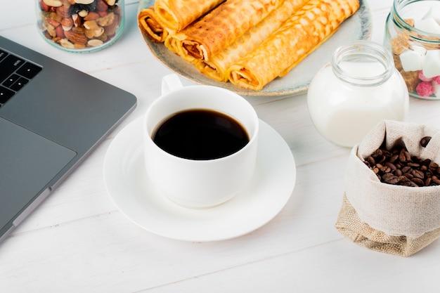 Vista lateral de una taza de café con rollos de obleas y portátil sobre fondo blanco.