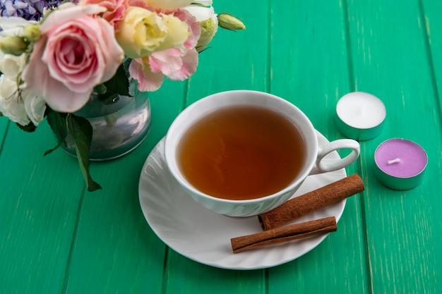 Vista lateral de la taza de té con canela en platillo y velas con flores sobre fondo verde