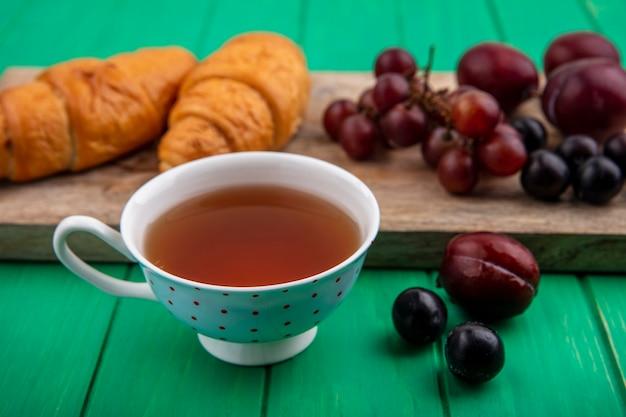 Vista lateral de la taza de té con croissants pluots de uva y endrinas en la tabla de cortar y sobre fondo verde