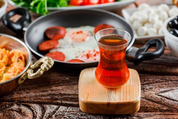 Vista lateral de una taza de té con deliciosas comidas en superficie de madera