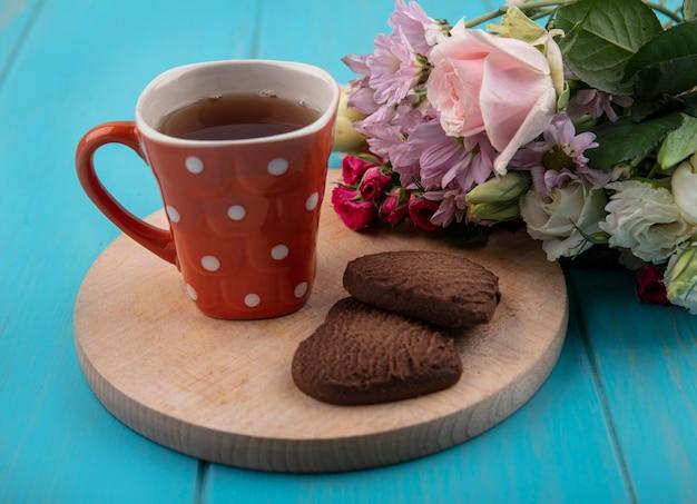Vista lateral de la taza de té y galletas en forma de corazón en la tabla de cortar con flores sobre fondo azul.