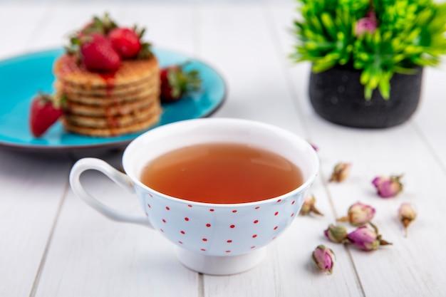Vista lateral de la taza de té y galletas waffle con fresas en plato y flores sobre superficie de madera