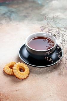 Vista lateral de una taza de té negro taza de té galletas ramas de los árboles