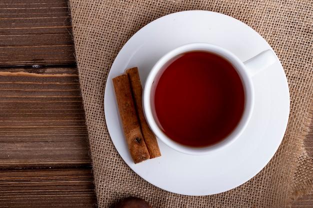 Vista lateral de una taza de té con palitos de canela en un rústico