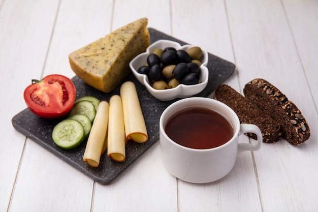 Vista lateral de una taza de té con quesos ahumados con aceitunas tomate pepino y rebanadas de pan negro sobre un fondo blanco.