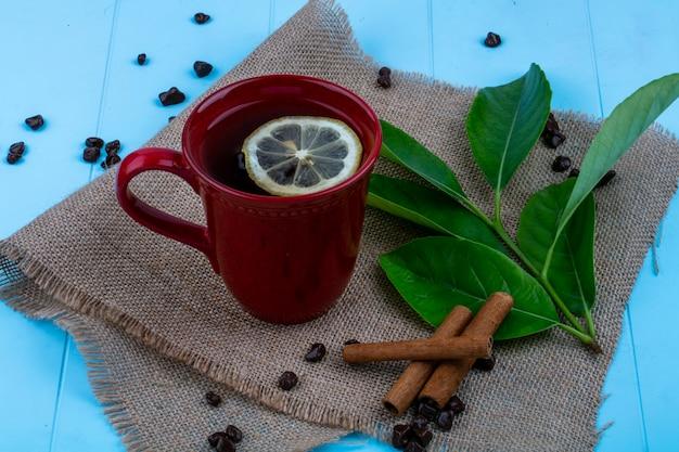 Vista lateral de la taza de té con rodaja de limón y canela con hojas y trozos de chocolate sobre tela de saco sobre fondo azul.