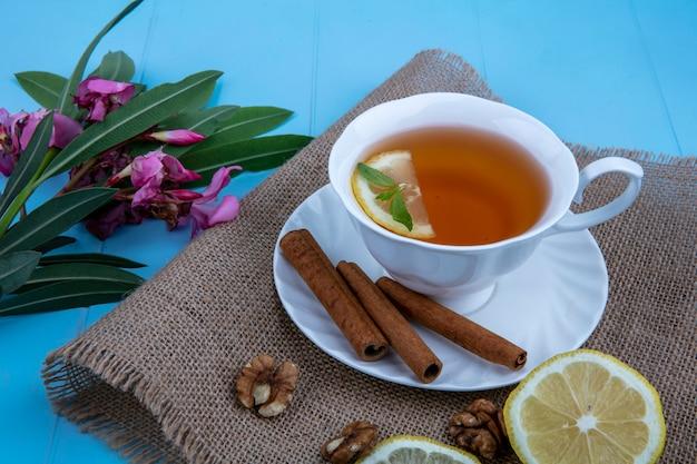 Vista lateral de la taza de té con rodaja de limón y canela en platillo con nueces rodajas de limón sobre tela de saco con flores y hojas sobre fondo azul.