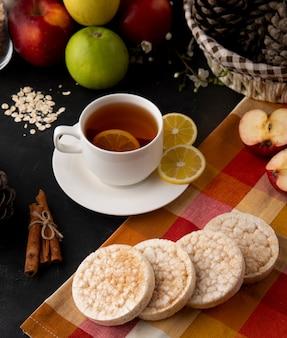 Vista lateral taza de té con rodajas de limón y canela con manzanas sobre la mesa