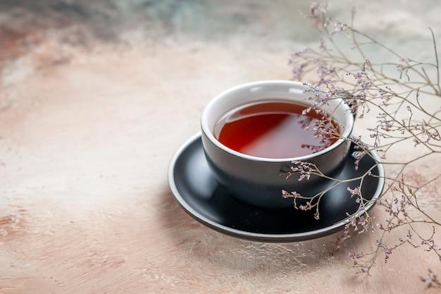 Vista lateral de una taza de té una taza de té en el platillo negro junto a las ramas de los árboles