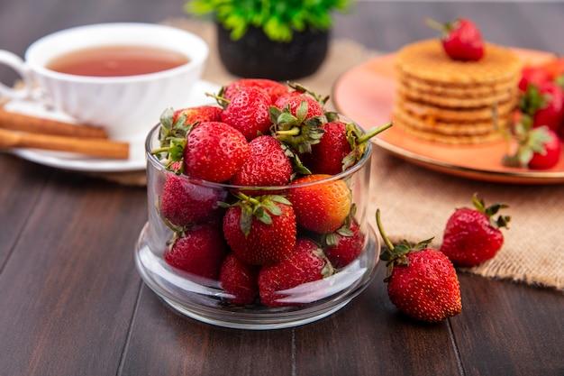 Vista lateral del tazón de fresa con una taza de té y canela y galletas waffle sobre tela de saco y superficie de madera