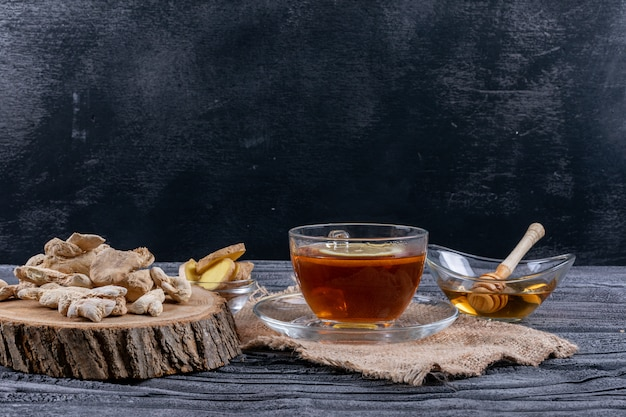 Vista lateral de un té con jengibre, rodajas y miel sobre tela de saco y fondo de madera oscura. horizontal