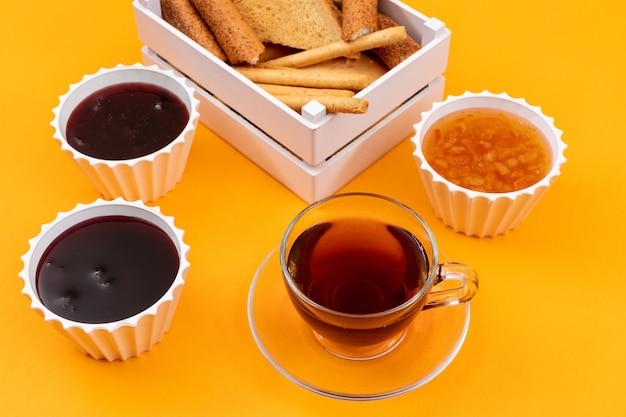 Vista lateral de té con mermelada y tostadas en superficie amarilla horizontal