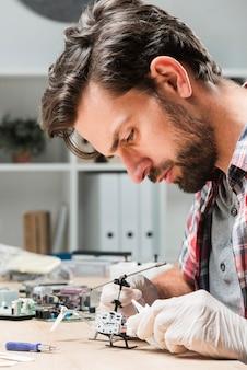 Vista lateral del técnico masculino joven que repara el juguete del helicóptero en el escritorio de madera