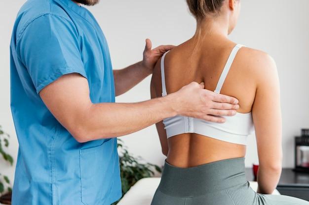 Vista lateral del terapeuta osteopático masculino comprobando el hueso de la escápula del paciente femenino